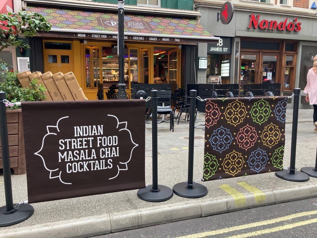 Papa Dum Restaurant in London City Centre. Indian street food cuisine in the capital of England. Bespoke branding for the awning, valance and cafe barrier banners all over printing in full colour by Parker Masters Ltd.