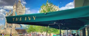 The Ivy Restaurant Tower Bridge in Central London. British brasserie with large terrace in the heart of England. Commercial parasol printed in gold to the valances.